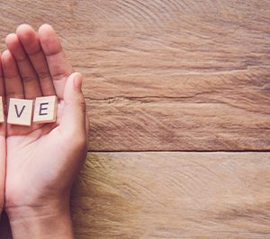 Letters spelling 'give' in hands